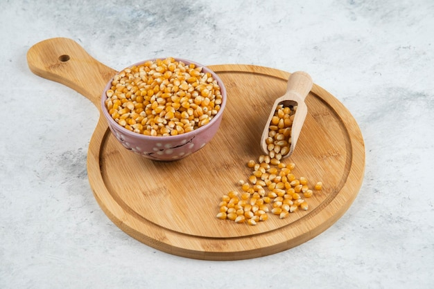 Bowl of uncooked corn grains with spoon on wooden board.