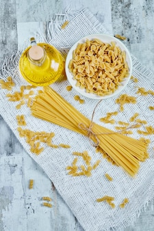 A bowl of uncooked pasta and spaghetti with oil and tablecloth.