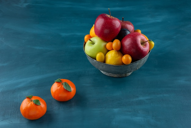 Bowl of various fresh fruits placed on blue surface.