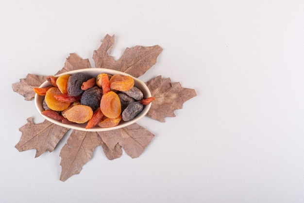 Bowl of various organic fruits with dry leaf on white background. high quality photo