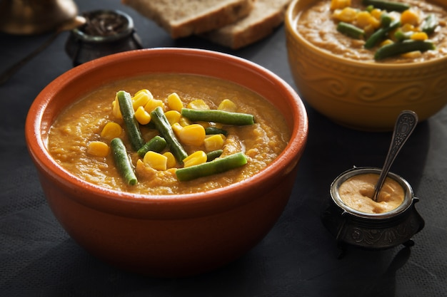 Bowl of vegetable pumpkin puree soup with corn