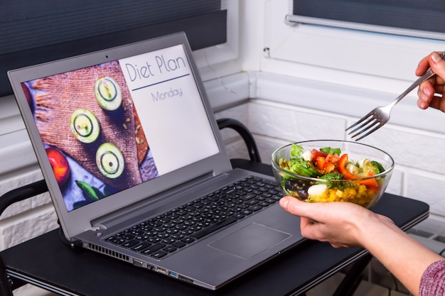 Bowl of vegetable salad in female hands near the laptop on the desktop