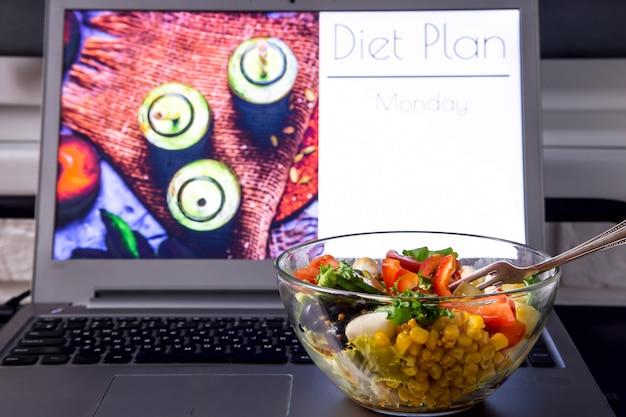 Bowl of vegetable salad near the laptop on the desktop