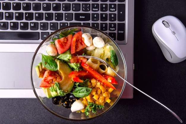 Bowl of vegetable salad with mozzarella, lettuce, tomato, pepper and cucumber on the desktop next to the computer mouse