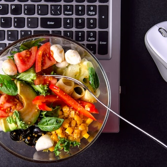 Bowl of vegetable salad with mozzarella, lettuce, tomato, pepper and cucumber