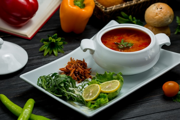 A bowl of vegetable soup in a broth served with lemon and green salad