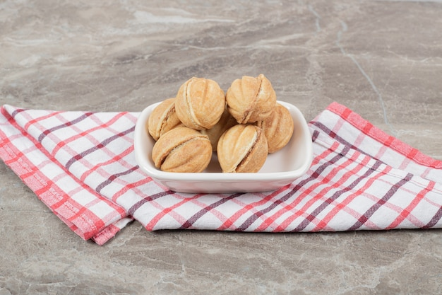 Bowl of walnut shaped cookies on tablecloth. high quality photo