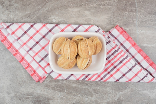 Ciotola di biscotti a forma di noce sulla tovaglia.