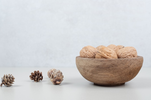 Bowl of walnuts and pinecones on beige surface