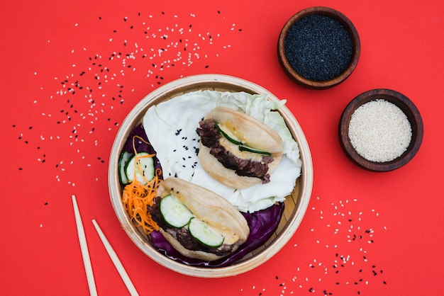 Bowl of white and black sesame seeds with gua bao in steamer on red backdrop