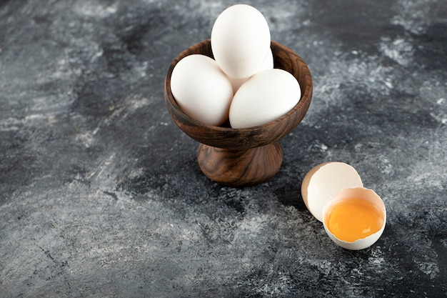 Bowl of white eggs and broken egg on marble surface.