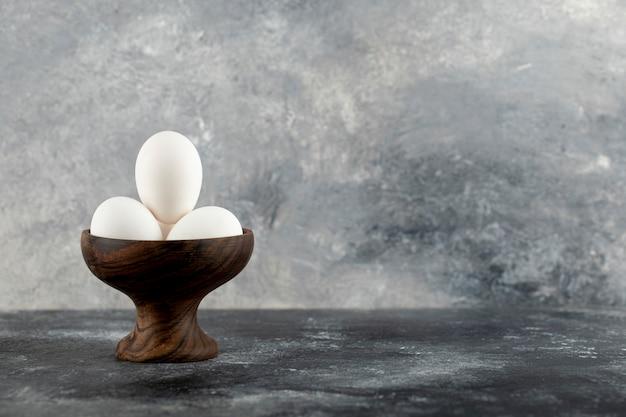 Ciotola di uova bianche sulla superficie in marmo.