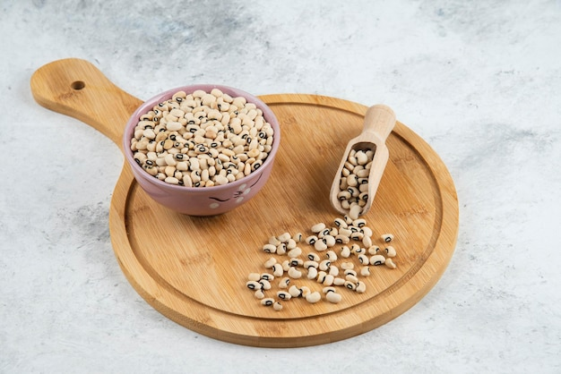Bowl of white kidney beans with spoon on cutting board.