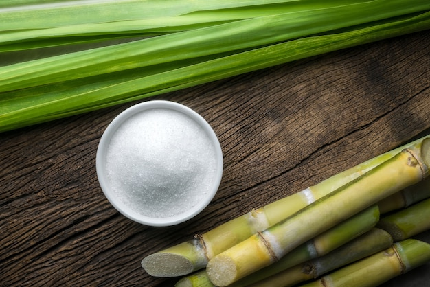 Bowl of white sugar with sugar cane on wood table
