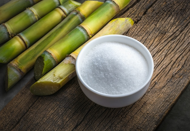 Bowl of white sugar with sugar cane on wood table .