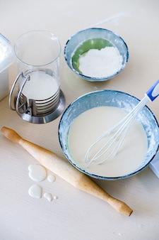 Чаша с венчиком и тесто для торта, блины или пончики, на деревенский деревянный стол. рядом мука, скалка, молоко в кувшине, капли теста. процесс выпечки и приготовления пищи в домашних условиях. семейная жизнь.