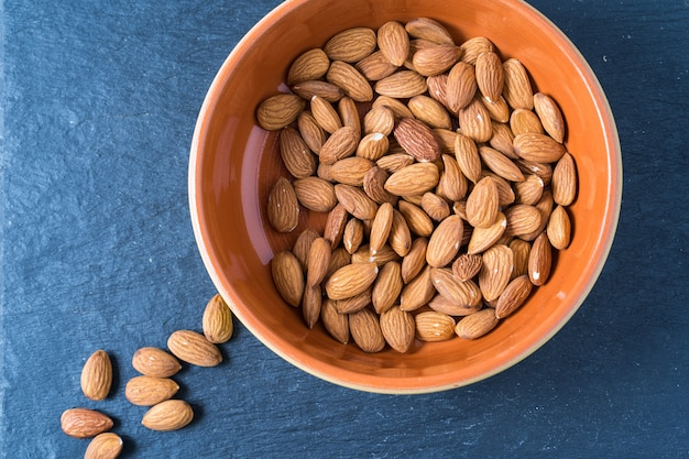 A bowl with almond nuts on gray background.