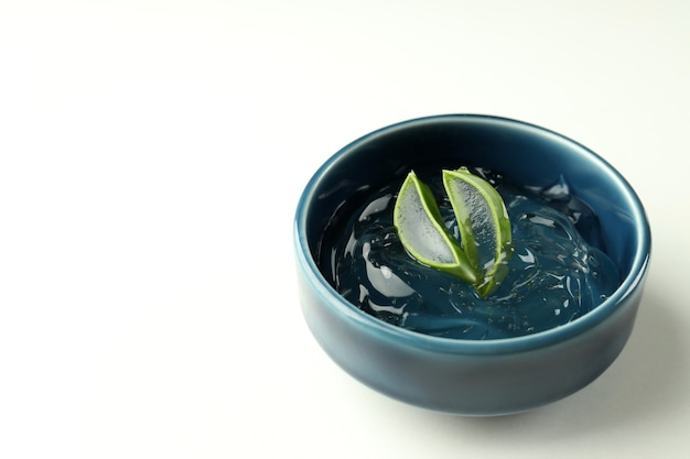 Bowl with aloe gel and slices on white background