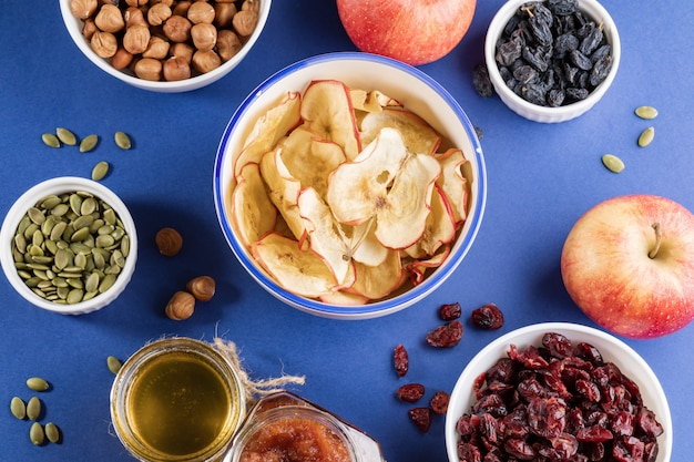 Bowl with apple chips surrounded by healthy snacks