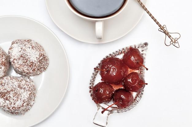 リンゴジャム、デザート、受け皿に飲み物と白い背景の上の銀のスプーンとカップ。