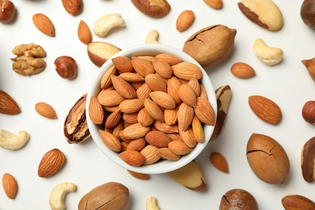 Bowl with apricot seeds and different nuts on white