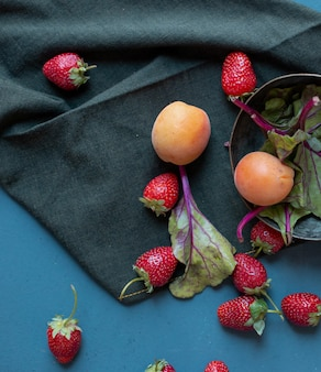 Bowl with apricots and spinaches inside and strawberries outside on a black mat.