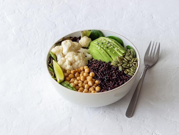 Чаша с авокадо, черным рисом, нутом, капустой, шпинатом и салатом. здоровое питание. вегетарианская пища.