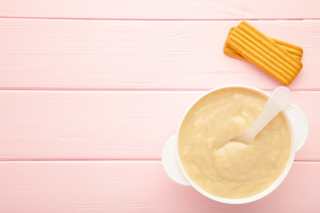 Bowl with baby food with biscuits on pink background