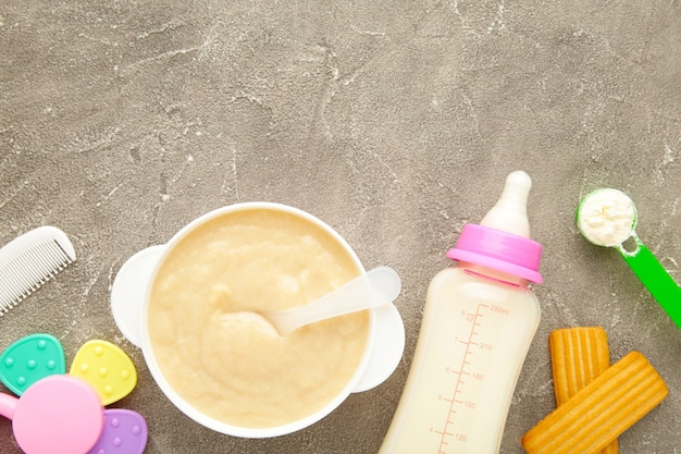 Bowl with baby food with toys on grey background