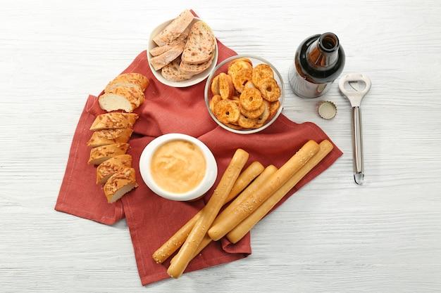 木製のテーブルにビールチーズディップと軽食を入れたボウル