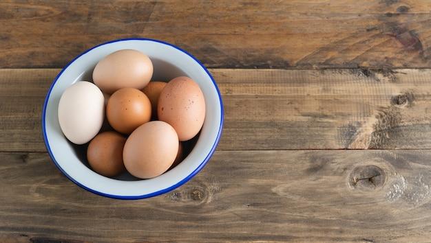 Чаша с вареными яйцами на деревянной поверхности. скопируйте пространство. вид сверху.