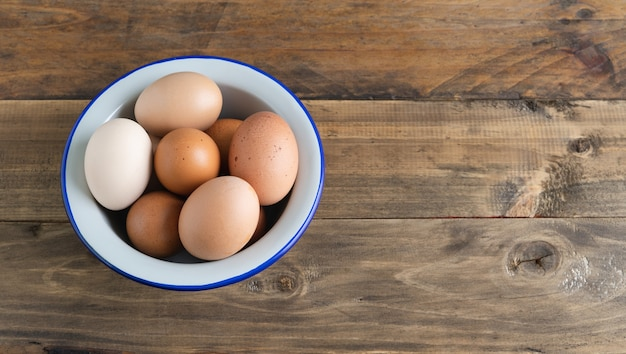Bowl with boiled eggs on wooden surface. copy space. top view.