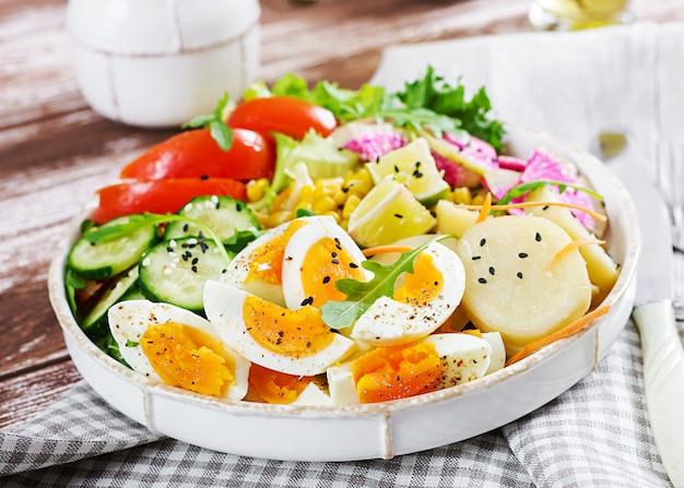 Bowl with boiled potato, cucumber, tomato, watermelon radish, lettuce, arugula, corn and boiled egg