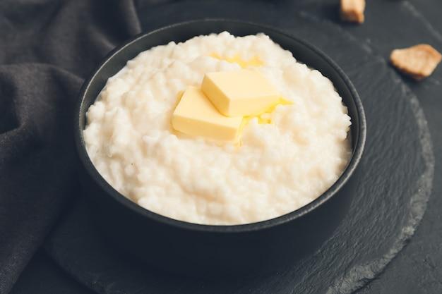 Чаша с отварным рисом и маслом на темном столе