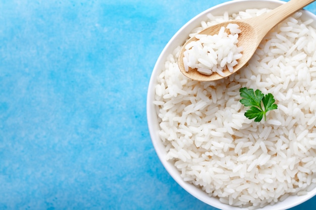 Bowl with boiled rice with green fresh parsley for delicious healthy lunch on a blue surfce.