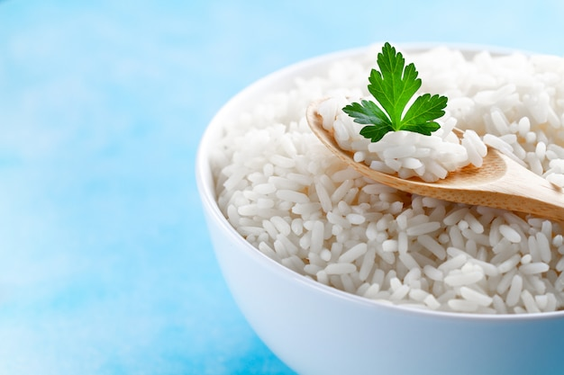 Bowl with boiled rice with green fresh parsley for delicious healthy lunch