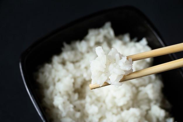 Чаша с вареным белым рисом на черном фоне. азиатская еда и бамбуковые палочки для еды.