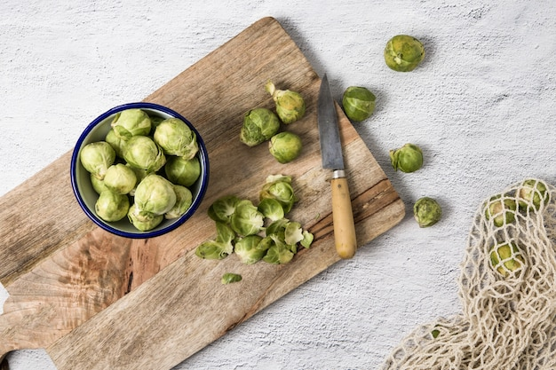 A bowl with brussel sprouts over a wood cutting board