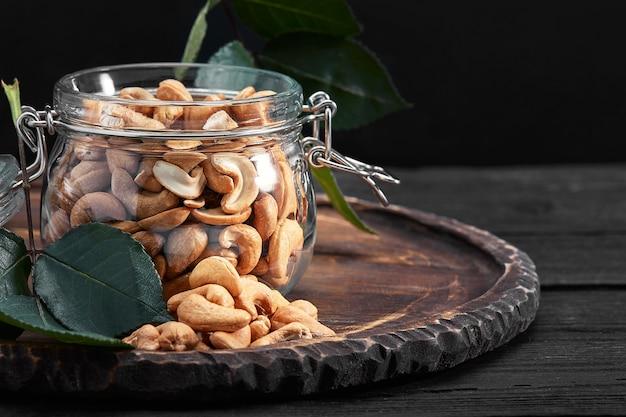 木製のテーブルの上にカシューナッツとボウル。珍味。