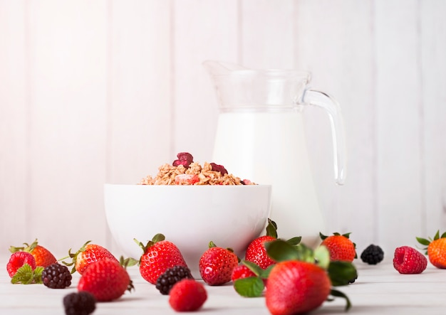 Bowl with cereal and fresh berries and jar of milk.healthy summer breakfast