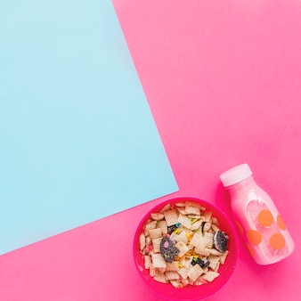 Bowl with cereals and pink milk bottle
