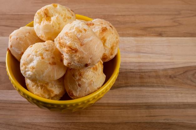 나무 테이블에 치즈 빵과 함께 그릇.