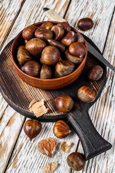 木製のテーブルの上に栗のボウル。上面図。