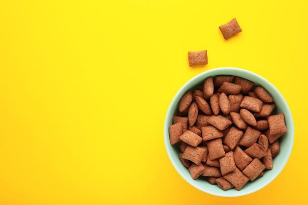 Чаша с шоколадными подушками на желтом фоне. вид сверху