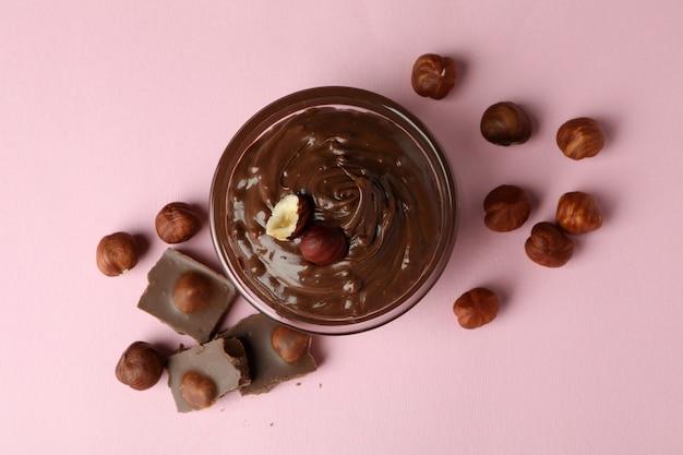 분홍색 배경에 초콜릿 페이스트, 견과류, 초콜릿을 넣은 그릇