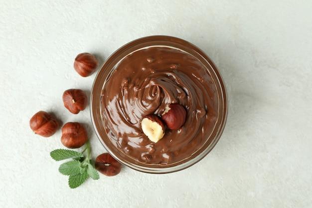 흰색 질감 배경에 초콜릿 페이스트, 견과류, 민트를 넣은 그릇