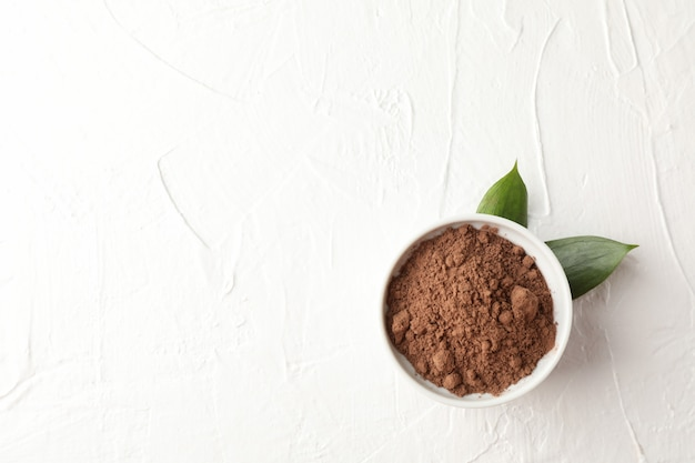 Bowl with cocoa powder and leaves on white, space for text