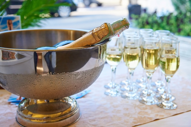 A bowl with cold champagne on the table with filled glasses.