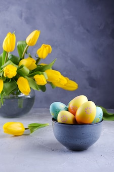 Bowl with colorful easter eggs; spring easter decoration on gray table with bouquet of yellow tulip flowers in glass vase; easter interior decoration