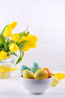 다채로운 부활절 달걀, 흰색 배경에 유리 꽃병에 노란 튤립 꽃의 부케와 흰색 나무 테이블에 봄 부활절 장식 그릇. 부활절 인테리어 장식